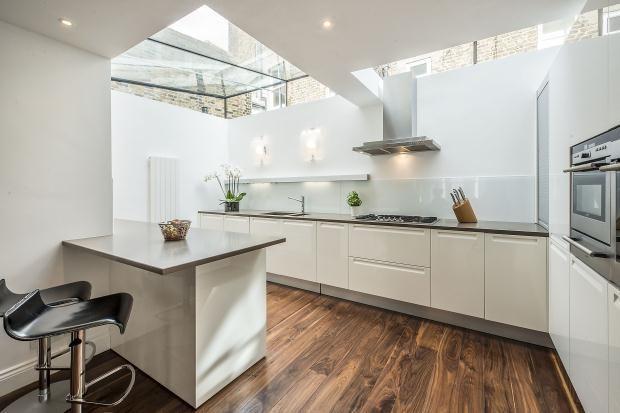 White splash-back, grey worktops & warm wooden floors make this high gloss white kitchen look warm.