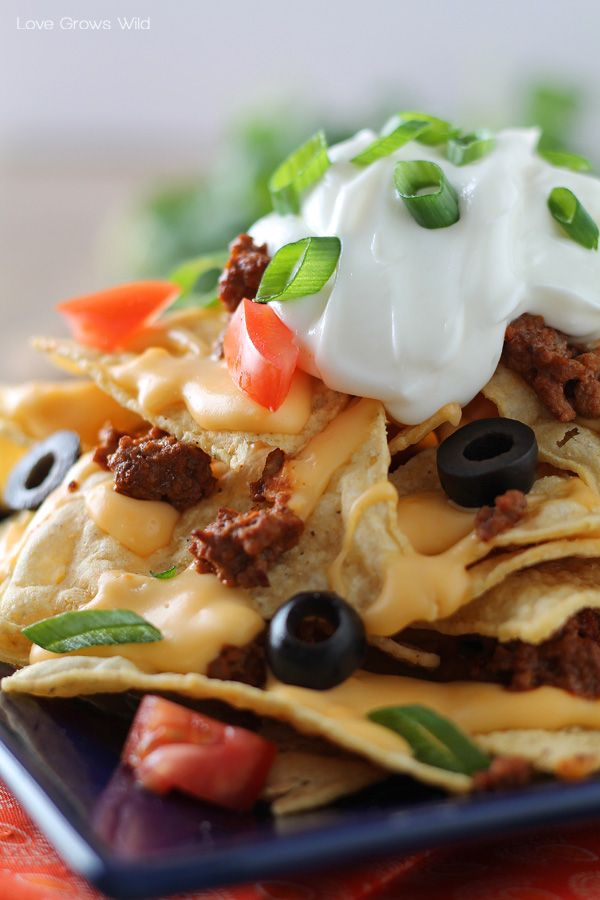 Chili Cheese Nachos Recipe ~ These nachos are piled high with layers of crispy tortilla chips, beefy chili, a homemade cheese sauce, and plenty of tasty toppings to make this the ultimate party food!