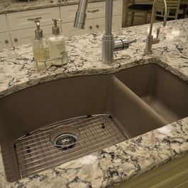 A Blanco SilGranit kitchen sink in the truffle finish is shown in an island with soft painted green cabinetry by Custom Cupboards. A patterned quartz countertop by Cambria in Bellingham color gives a texured