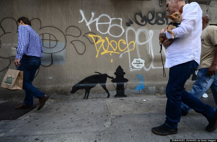 """People walk by a street art graffiti by elusive British artist Banksy, as part of his month-long """"Better Out Than In exhibit"""" in New York, October 3, 2013."""