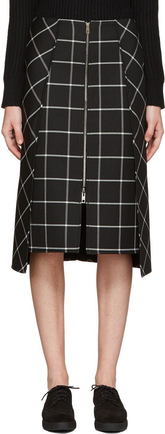 Mid-length wool-blend gabardine skirt featuring check pattern in black and white. Two-way zip closure at front. Overlay panel featuring twin vents at front hem. Central vent at back hem. Drop-tail hem. Tonal stitching.