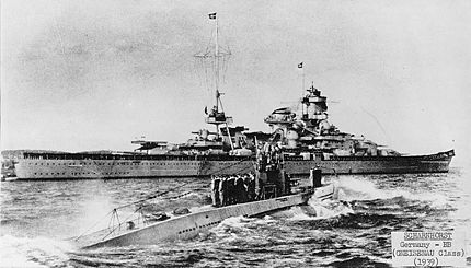 U-47 returns to port after sinking HMS Royal Oak. The battleship Scharnhorst is in the background.  October 14, 1939 U-47, under Kapitänleutnant Günther Prien, penetrates the British naval base at Scapa Flow, sinking HMS Royal Oak at anchor.