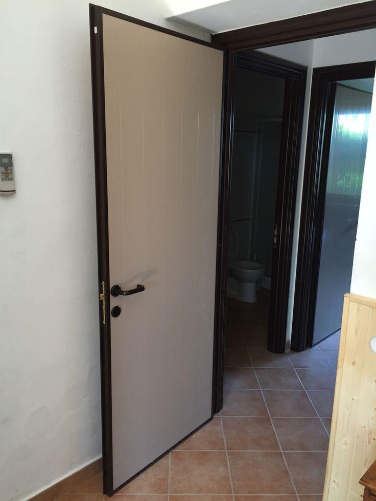 Porta interna in Pvc, con pannello liscio beige, cornicetta, telaio, coprifili e maniglia marrone.