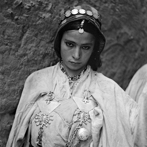 - Besancenot Jean (1902-1992) - Femme juive drapée de l'izar blanc journalier retenu par deux fibules d' argent, khelalat. La coiffure est formée de la perruque de poils de bovins recouverte d'un foulard serré par un diadème de douros, sfifa. - Arago