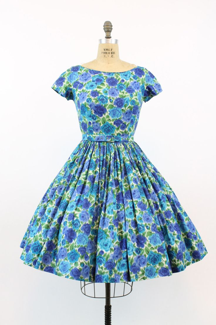Gorgeous 1950s cotton dress! Made in a bright blue, green, and ivory floral watercolor design. Center back metal zipper. Nipped in waistline with a