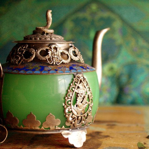 This green jade ANTIQUE TIBETAN TEA POT is intricately decorated with a silver coiled snake on the lid and a majestic dragon on the side. It has detailed floral cloisonné enamel around the rim, and a tiny frog perched upon the handle. The rustic round tin has a mandala design and a perforated top.