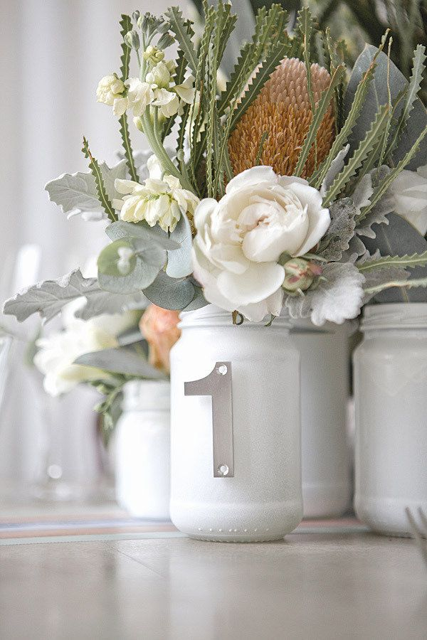 Help guests find their seat by stringing table numbers from Mason jar centerpieces, like this one styled by Emily Vawser of Gold Dust.