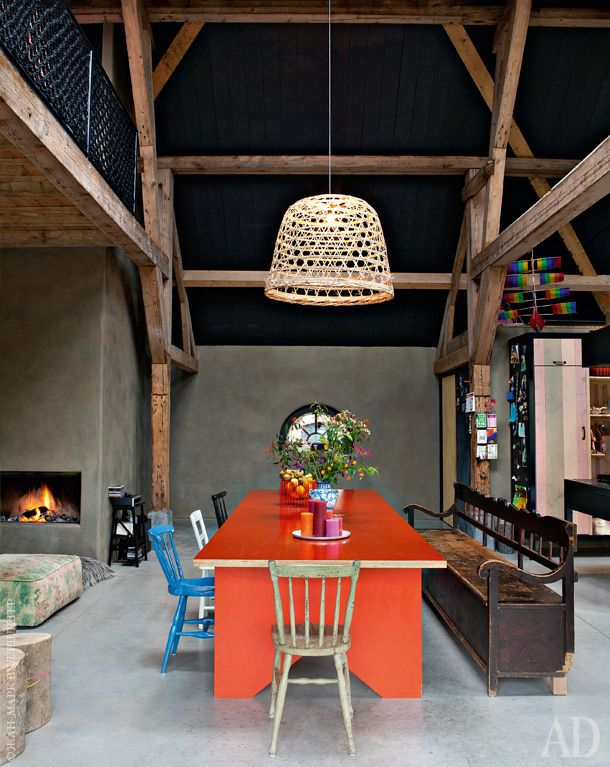 В обеденной зоне— наливной пол избетона. Оранжевый стол сделан назаказ.