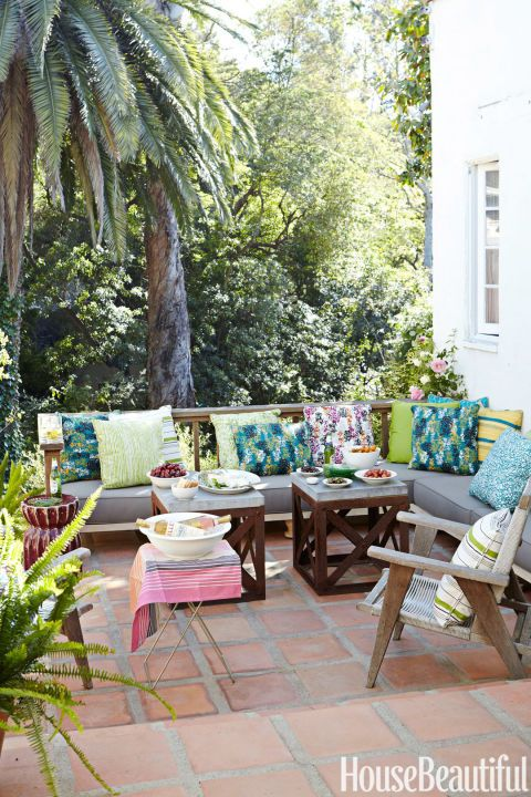 MONTECITO –On the terrace off Chris Barrett's L.A. house, midcentury armchairs and stone-topped iron tables provide an aged contrast to the L-shaped banquette. For the pillows on the top, Barrett designed outdoor fabrics inspired by vintage wallpaper and textiles. Patterns include Montecito and Monteray. Click through for more outdoor fabric ideas.