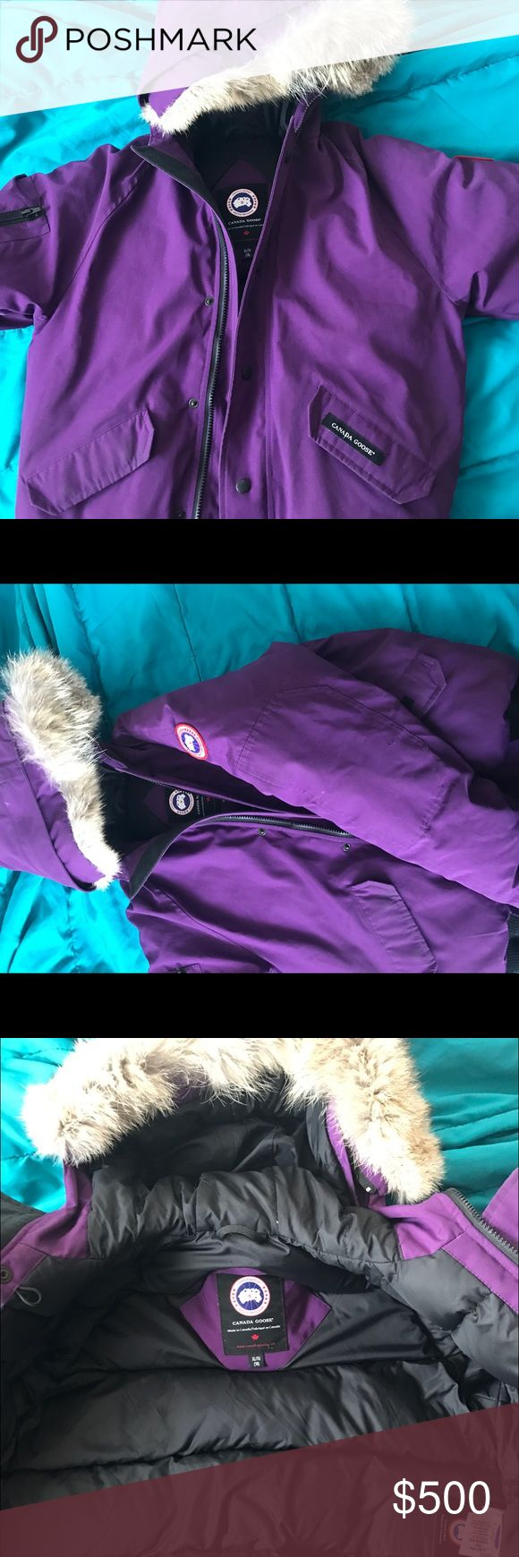 Purple Canada Goose Bomber Jacket Outershell: 85% polyester/15% Cotton. Lining: 100% nylon. Fill: 625 Fill power with 80/20 Canadian White Duck Down. Fur: Natural Coyote from Canada Machine wash Imported Zip removable hood with genuine fur trim Long sleeves with left logo patch, right zip pocket and contrast ribbed cuffs Front zip closure with exterior snap placket Two snap flap side pockets, interior mesh pocket, interior zip chest pocket Contrast ribbed hem Real whole coyote fur imported…