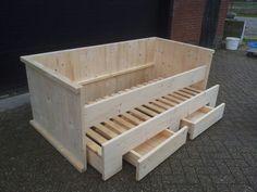 Kinderbed van steigerhout met logeerlade en speelgoedlades.