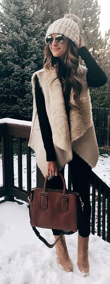 Women's black long sleeve top with brown fur vest