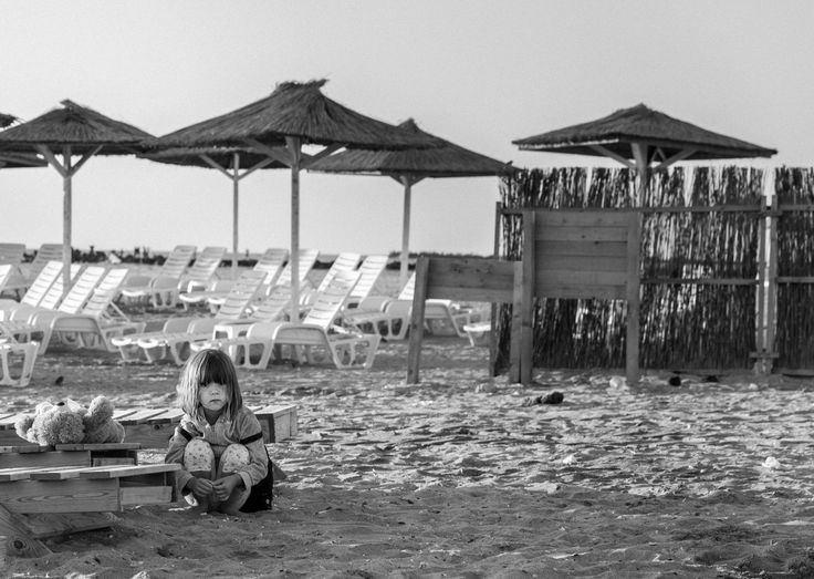 lone child on a beach, photography, picture, art, painting, black and white, gray, brown, grayscale, old, eye, eyes, female, woman, lady, young, baby,