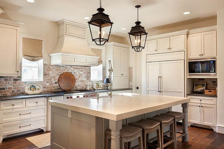 Cottage kitchen boasts a pair of carriage lanterns illuminating a gray center island fitted with a ...