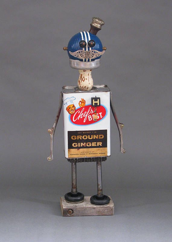 """CHEF HAL is a one-of-kind robot sculpture. This whimsical robot sculpture is created from found and discarded objects which include a tin can, wooden handle, croquet ball, jewelry beads, jewelry pieces, wooden number game piece, kitchen tongs, cookie cutter, biscuit cutter, rubber wheels, and industrial scrap metal. Chef Hal is not a toy nor is he functional, except to make you smile or laugh! - SIZE: 17.25"""" tall by 7"""" wide by 3.25"""" deep - Chef Hal can be displayed on a console table…"""