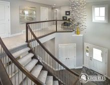 Open-to-above Foyer with open-riser, curved staircase. The Onyx model Showhome built by Kimberley Homes in Ambleside (Windermere), Edmonton, AB  #curvedstaircase #foyer #interiordesign #newhomedesign #homedesign #newhome #customhome #yegre #buildwithkimberley #kimberleyhomes