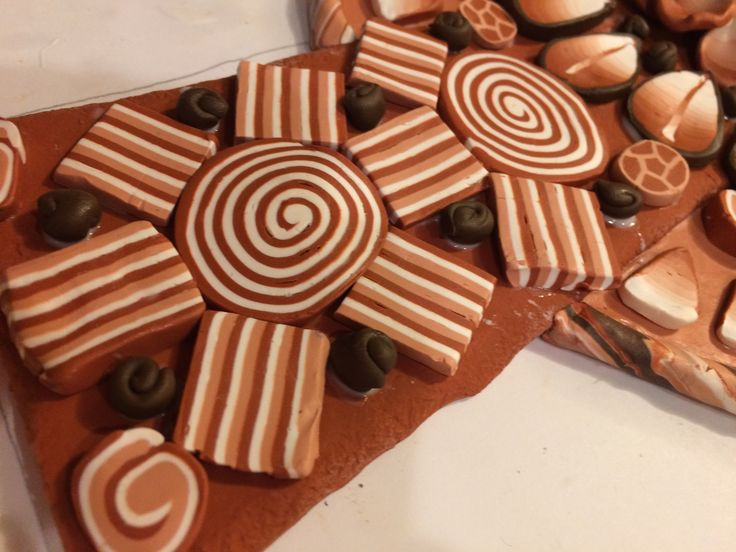 Terracotta and white polymer clay cross close-up showing sliced canes. By Pat Brown