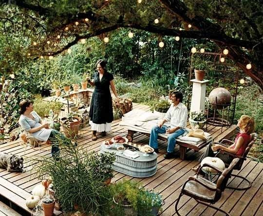 Love turning the metal tub upside down for an outdoor table. Also love the combination of wood, metal, and lights among all the greenery.