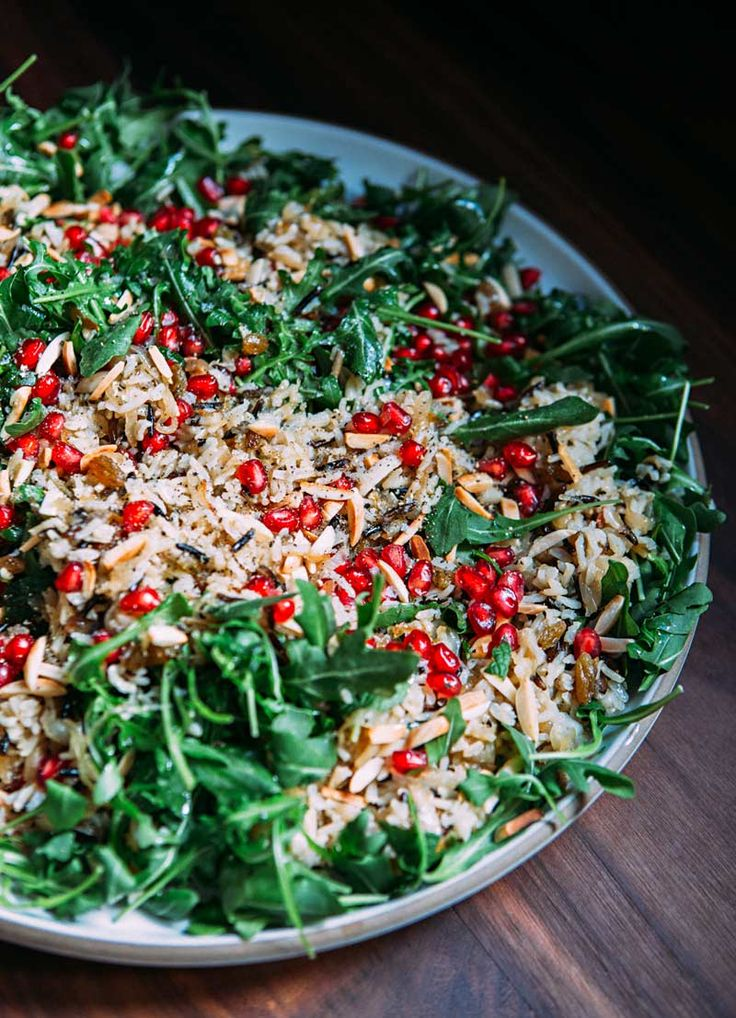 Spicy Warm Winter Salad - Image Via: A House in the Hills (5 oz baby arugula, 5  medium shallots, thinly sliced, 1/2 cup blanched almond slivers, 1/2 cup golden raisins, 1 cup torn mint leaves, 1/2 cup pomegranate seeds, 4 + tablespoons extra virgin olive oil, 4 cups cooked rice (1/2 wild rice, 1/2 basmati rice)