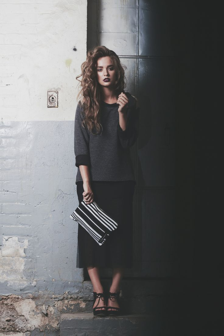 | Laurie Brown | Marino wool sweater with shoulder cut outs. Black sheer mesh skirt. Black and white stripe clutch.
