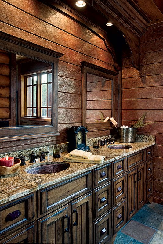Faux-painted texture applied to the pine walls results in a rich copper tone in the master bathroom. Highly veined granite brings out the rich hue of the knotty-alder cabinets from Cutting Edge Millworks. Crown molding and twin hammered-copper sinks add a touch of elegance.