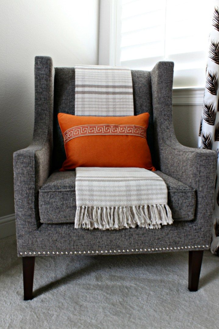Modern wingback chair, orange pillow with Greek key trim, and plaid throw from Pretty Practical Home.
