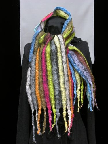"""Merino wool felted on black silk (Nuno felt). Design has two color palettes of stripes (one cool and dark, the other warm and bright); stripe palettes are staggered and alternated 4 times. 1st color palette: 3 grays, orange, khaki, fuschia, lime, and light yellow. 2nd palette: sky blue, lime, reddish brown, lavender, light gray and aqua. Felted fringe on each end is 5""""long (and included in total length).  Metallic yarn is felted on one side only, but rich colored stripes are repeated on each…"""