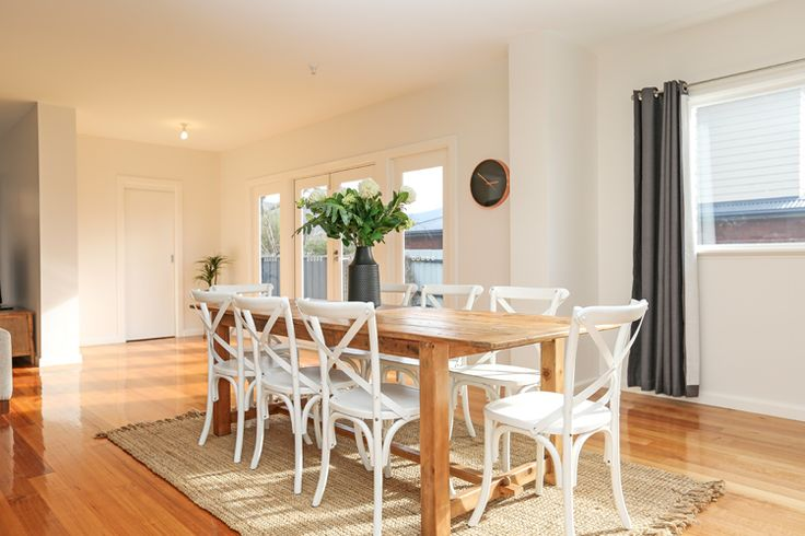 Contemporary dining, family home, polished floorboards, timber dining table, white cross back dining chairs, jute rug, matte black vase, gunmetal grey curtains
