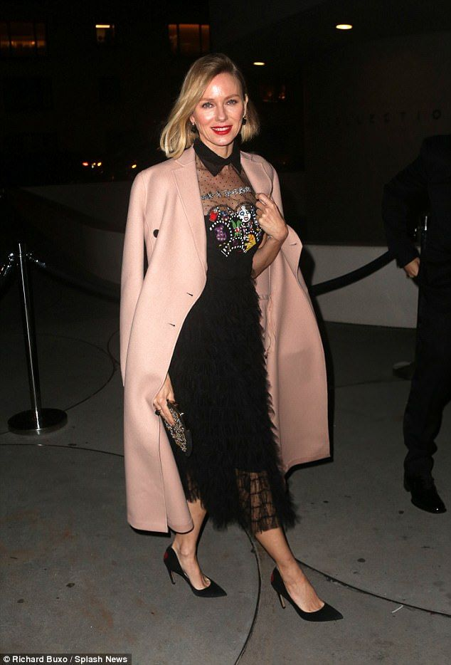 Bracing herself from the cold:Keeping warm, Naomi added a dusty pink overcoat to her ense...