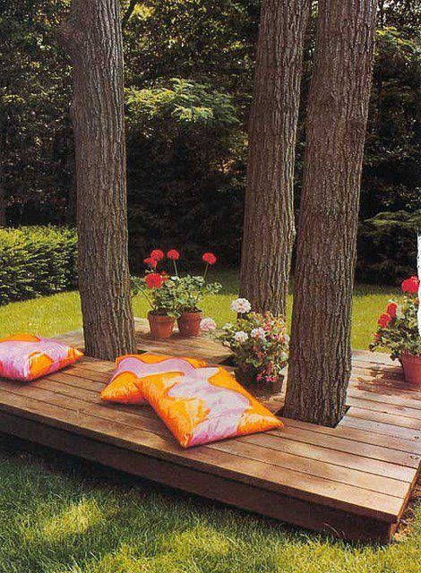 Relaxing spot for summer reading ~ shady deck built around trees with bright pillows and flowers!!