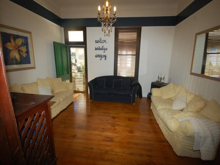 Lounge room - after photo - gas log fire place in the corner - 3x3 seater sofas - polished timber floors -
