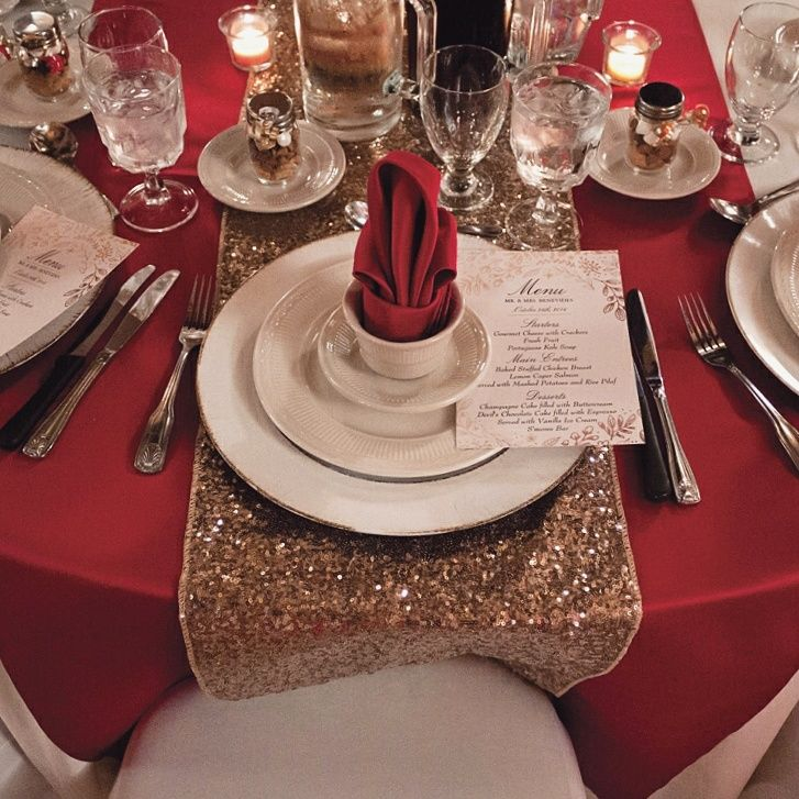 Place setting from a gorgeous autumn themed wedding! Apple red runners accented with gold sequin table runner! Rustic charges anchor the place setting head together with a specialty menu and satin apple red napkin folds!