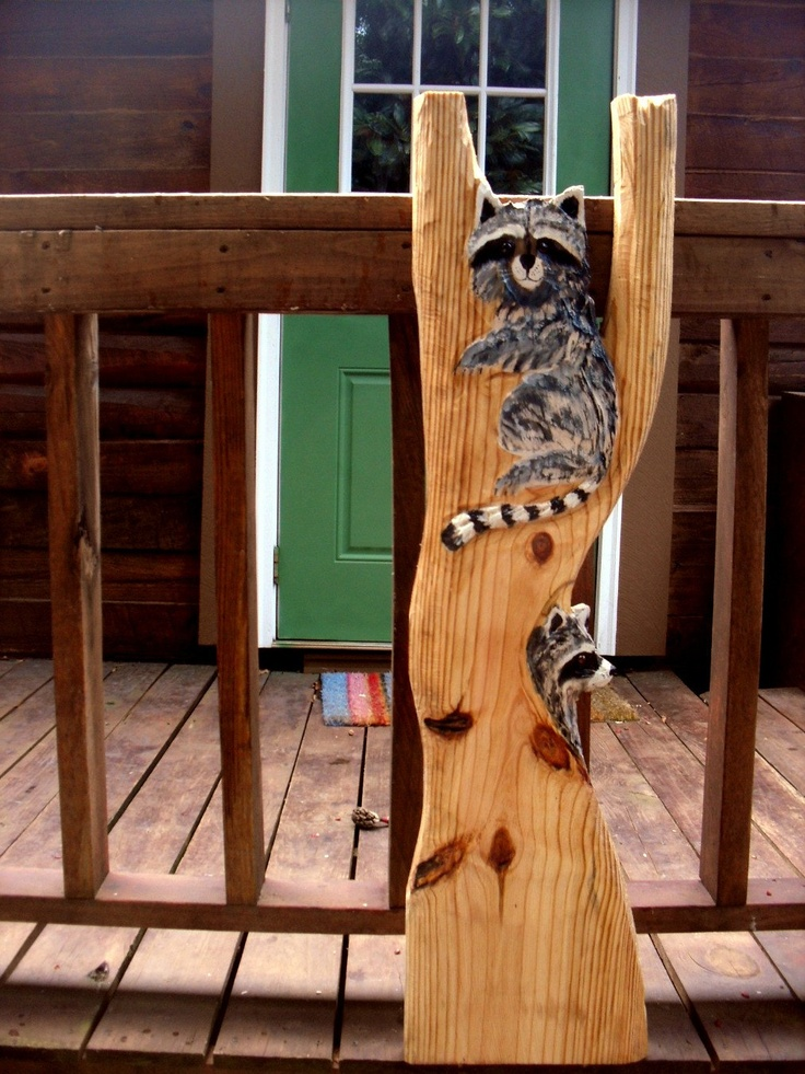 Two raccoons in tree chainsaw wood carving by