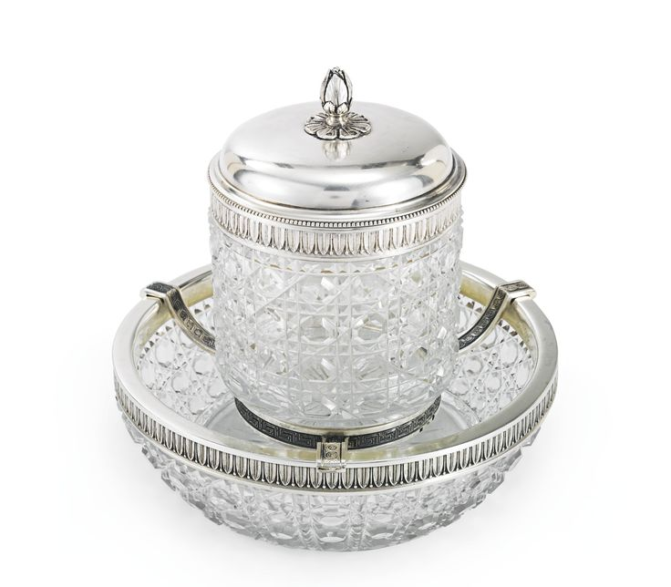 A Russian silver-mounted cut glass caviar serving set, Petr Fariseev, Moscow, 1908-1917, the cut glass ice bowl and caviar dish set with silver mounts stamped and chased with a leaf tip pattern, suspended on a three-armed mount stamped with Neoclassical motifs, the slip-on cover with bud finial.