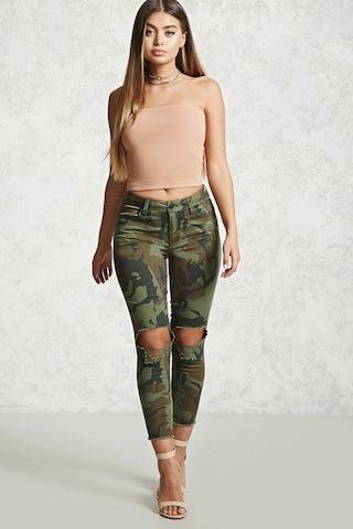 A pair of woven skinny pants featuring an allover camouflage print, a mid-rise fit, distressed details, whiskering, a five-pocket construction, a raw-cut frayed hem, and a zip fly.