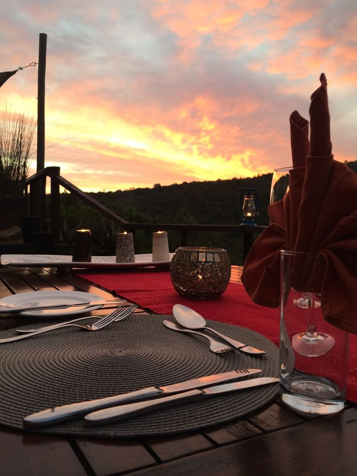 Dinner setting on the deck at sunset at Sibuya Bush Lodge.  Kenton on Sea, Eastern Cape, South Africa www.sibuya.co.za