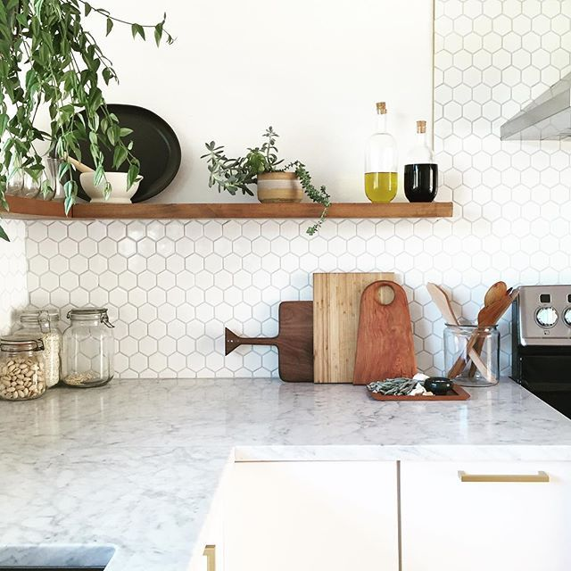 marble counter + white hexagon tile backsplash + wood shelving