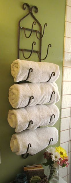 a wine rack repurposed to store four white towels