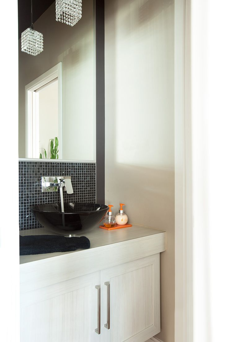 Simple et élégante, les armoires de cette salle d'eau en polyester, comprenant un comptoir en stratifié identique, se marie très bien à la jolie vasque en verre – en harmonie avec la mosaïque murale.