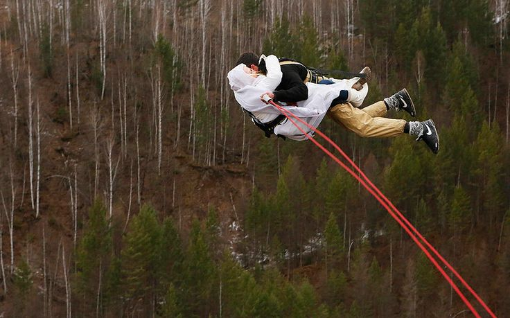 A newly married couple, members of the amateur rope-jumping group 'Exit Point', jumps from a 44-metre high (144-ft) water pipe bridge in the Siberian Taiga area outside Krasnoyarsk, Russia. Rope-jumping, an extreme sport, involves jumping from a high point using an advanced leverage system combining mountaineering and rope safety equipment. Picture: Ilya Naymushin/Reuters