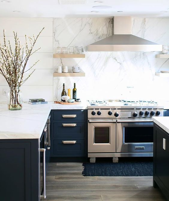 Kitchen with navy cabinets and marble countertops and backsplash