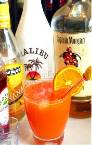 ¾ ounce Coconut Rum (Malibu) ¾ ounce Banana Liqueur (Hiram Walker) 1 ounce Spiced Rum (Captain Morgan) 1.5 ounce Orange Juice 2.5 ounce Pineapple Juice 2-4 dashes (1-2 tablespoon) Grenadine ¼ cup crushed ice   Garnish: Orange/Pineapple wedge 1 Maraschino Cherry (optional)