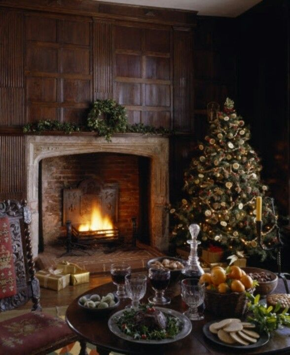 Wonderful fireplace against old wood panelling - fruit and cut crystal on the table. Warm and authentic setting for a traditional Christmas