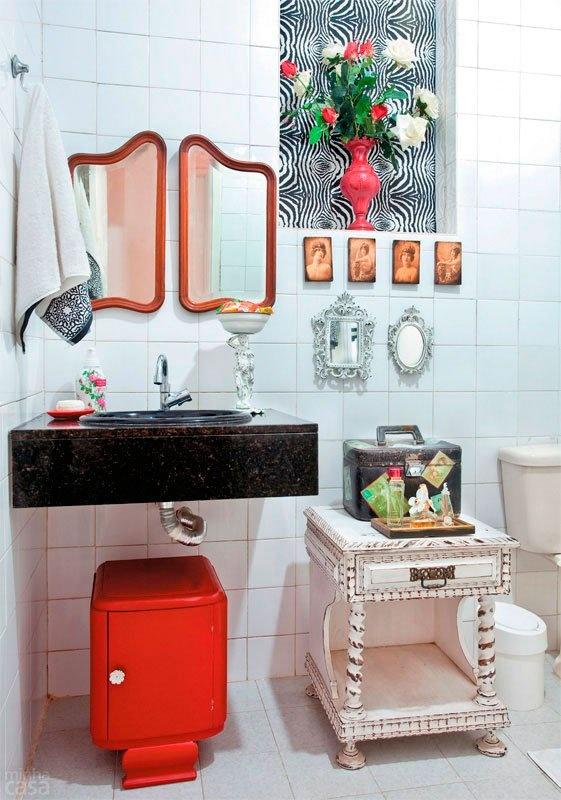 Vários destaques no banheiro projetado por Valentina Rocha: criado-mudo manuelino, o gabinete art nouveau laqueado de vermelho e a janela coberta de tecido.