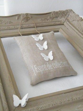 Coussin de porte lin naturelInscription 'ESPRIT DE COLLECTION' peinture textile (voir options)Agrémenté de 3 papillons double en papier cartonné blanc casséLien ficelle ancienneDimensions : 15,5cm x 11,5cm (env.)