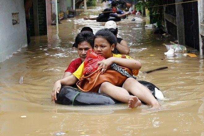 By Thursday morning (17/1/13) nearly 20,000 people had been evacuated from their homes, including this woman being floated out on January,16 2013 | Reuters