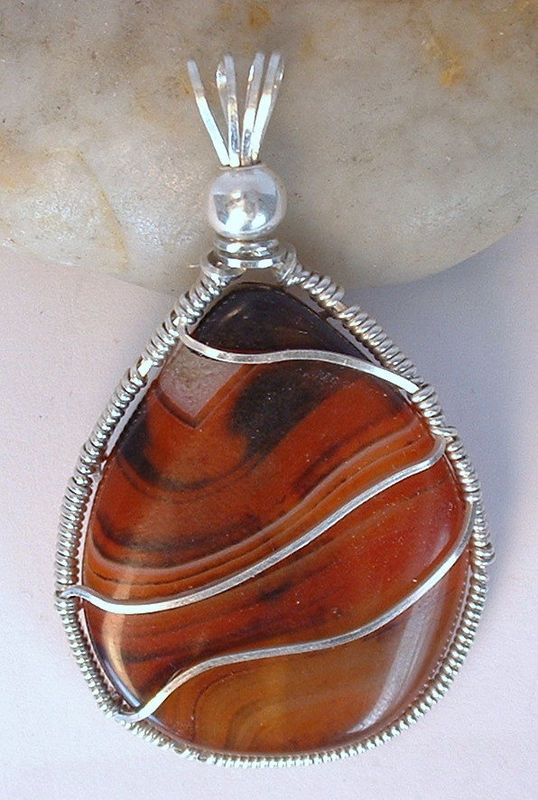 Wrapping with the lines of the stone enhances the beauty of the pattern of this Red Banded Agate pendant, and creates a harmony between the stone and the wire. I wrapped it in Argentium sterling silver square wire in a way that emphasizes the curv...
