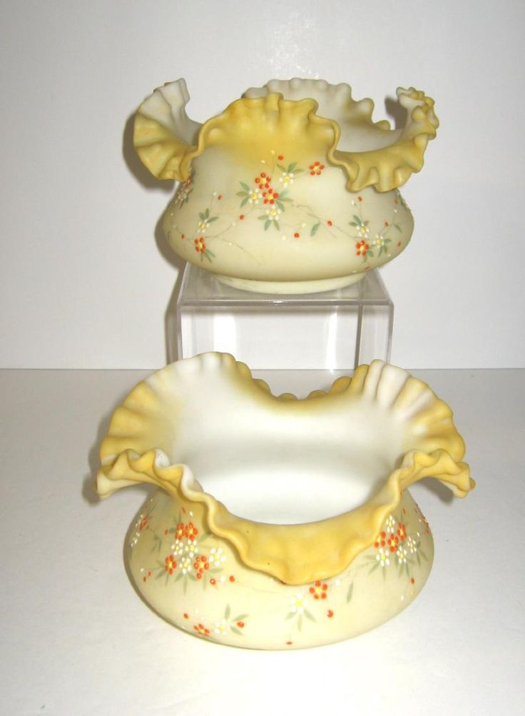 Mt. Washington brides basket..Two ruffled rim Mt. Washington Crown Milano bowls decorated with orange and white flowers set in an original marked Pairpoint two arm caddy with central stem design of a caged bird and a cherub finial