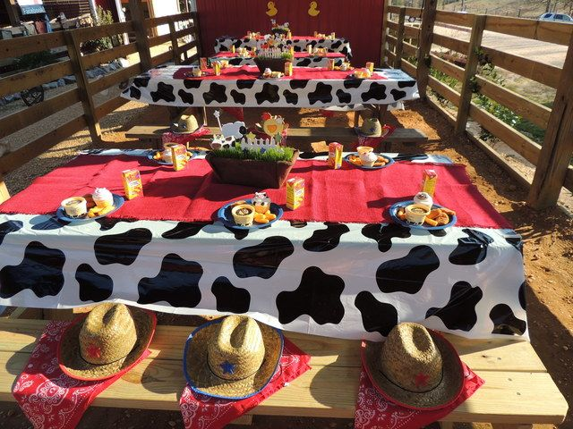 Farm party tables - cow print tablecloths, hats and bandanas for guests