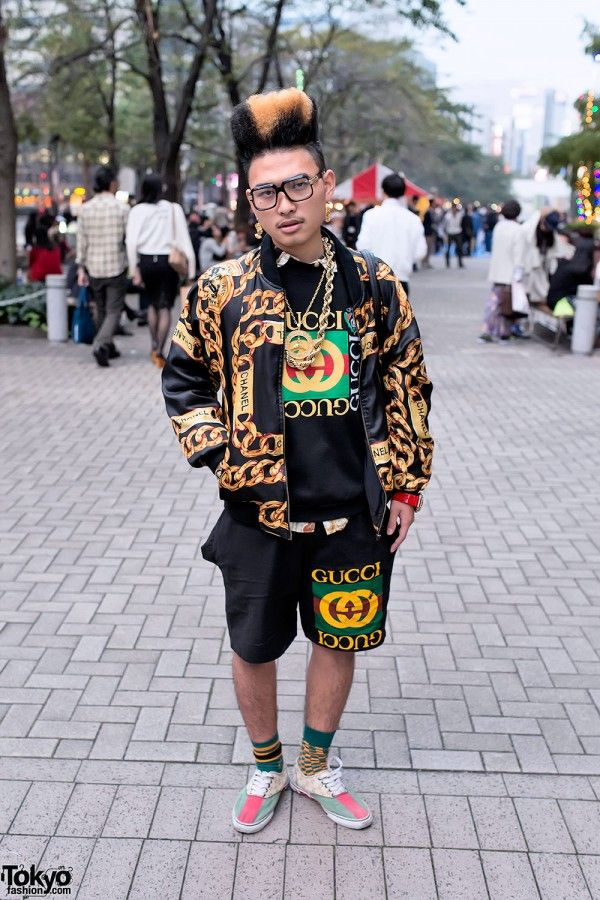 """Buraian is wearing a bootleg Chanel jacket (he told us most of his items are """"boot"""") with a bootleg Gucci top, bootleg Gucci shorts, and Ti$A slip on sneakers. Accessories include lots of gold chains, an Egyptian-inspired gold earring, and a Versace bag."""